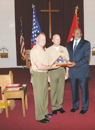 Maj. Gen. John J. Broadmeadow, commanding general, presents Gerald Dixson (right), an American flag, during his retirement ceremony at the Chapel of the Good Shepherd, here, in October. They and Sgt. Maj. Joseph M. Davenport (center) are all with Marine Corps Logistics Command.