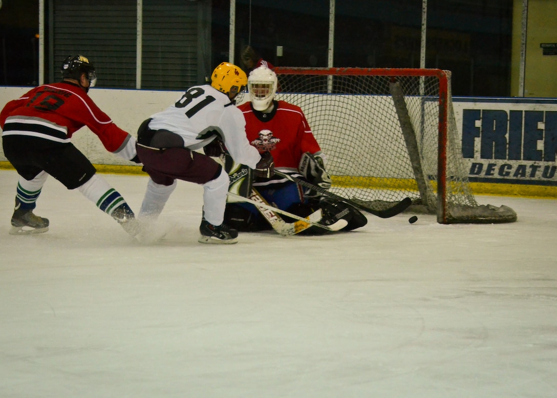 Airman 1st Class Matthew Gaffney, a hockey player with the Brew City Tankers, a team representing the 128th Air Refueling Wing, shoots the puck into the goal of the Badger Militia, a hockey team representing the 115th Fighter Wing and Wisconsin Joint Force Headquarters, at the 2014 Armed Services Hockey Tournament at the Sobe Ice Arena in Las Vegas Nov. 8, 2014.  (U.S. Air National Guard photo by Staff Sgt. Jenna V. Lenski/Released)