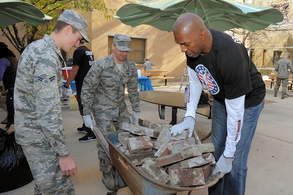Airman 1st Class Shane Coopmans (left), Staff Sgt. Albert Lamboy and Thurl Bailey, a former NBA player with the Utah Jazz, dispose of old bricks during a community service project Nov. 6, 2014, at the George E. Whalen Veterans Affairs Medical Center in Salt Lake City, Utah. Coopmans is with the 75th Operations Support Squadron and Lamboy serves with the 75th Logistics Readiness Squadron. (Air Force photo/Todd Cromar)