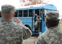 Soldiers look on as service members disembark a bus upon arrival at Langley Transit Center Nov. 13, 2014, at Langley Air Force Base, Va. Service members from multiple branches of the armed forces will undergo a 21-day controlled monitoring period at the transit center after returning from fighting the spread of Ebola in West Africa in support of Operation United Assistance. (U.S. Air Force photo/Staff Sgt. Jason J. Brown)