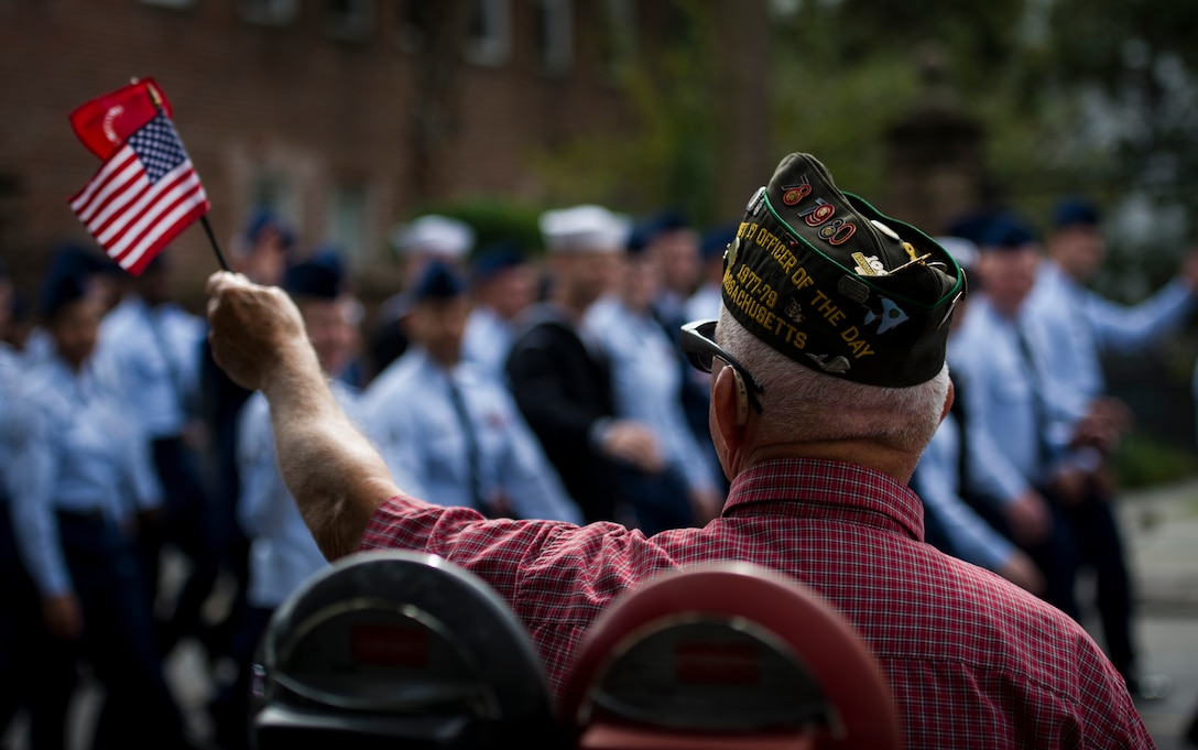 U.S. Marine Corps veteran Richard Starr waves an American flag as members of Joint Base Charleston march by while participating in the Ralph H. Johnson Veterans Hospital Annual Veterans Day parade Nov. 8, 2014, in Charleston, S.C. The origins of the holiday date back to President Woodrow Wilson, who proclaimed Armistice Day to mark the end of World War I. The armistice between Germany and the Allied nations that ended WWI was signed on that day and a ceasefire went into effect on the 11th hour of the 11th day of the 11th month in 1918. (U.S. Air Force photo/Airman 1st Class Clayton Cupit)