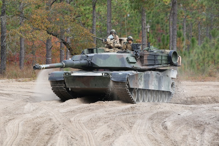 Marines with Tank Platoon, Company B, Ground Combat Element Integrated Task Force, command an M1A1 Abrams tank through the outside trails of Landing Zone Hawk aboard Marine Corps Base Camp Lejeune, North Carolina, Nov. 13, 2014. From October 2014 to July 2015, the GCEITF will conduct individual and collective level skills training in designated ground combat arms occupational specialties in order to facilitate the standards based assessment of the physical performance of Marines in a simulated operating environment performing specific ground combat arms tasks. (U.S. Marine Corps photo by Cpl. Paul S. Martinez/Released)