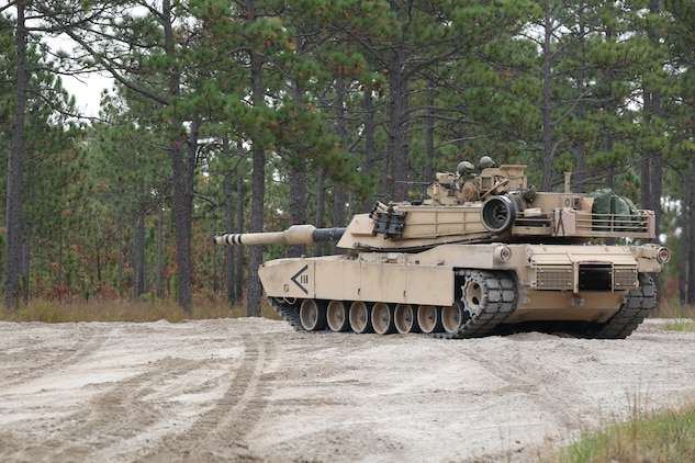 Marines with Tank Platoon, Company B, Ground Combat Element Integrated Task Force, use an M1A1 Abrams tank to conduct a situational assessment on the outside trails of Landing Zone Hawk aboard Marine Corps Base Camp Lejeune, North Carolina, Nov. 13, 2014. From October 2014 to July 2015, the GCEITF will conduct individual and collective level skills training in designated ground combat arms occupational specialties in order to facilitate the standards based assessment of the physical performance of Marines in a simulated operating environment performing specific ground combat arms tasks. (U.S. Marine Corps photo by Cpl. Paul S. Martinez/Released)