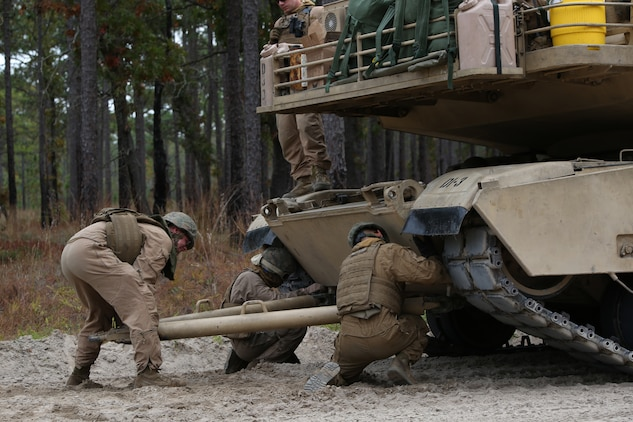 Marines with Tank Platoon, Company B, Ground Combat Element Integrated Task Force, conduct a land tow of an M1A1 Abrams tank on the outside trails of Landing Zone Hawk aboard Marine Corps Base Camp Lejeune, North Carolina, Nov. 13, 2014. From October 2014 to July 2015, the GCEITF will conduct individual and collective level skills training in designated ground combat arms occupational specialties in order to facilitate the standards based assessment of the physical performance of Marines in a simulated operating environment performing specific ground combat arms tasks. (U.S. Marine Corps photo by Cpl. Paul S. Martinez/Released)