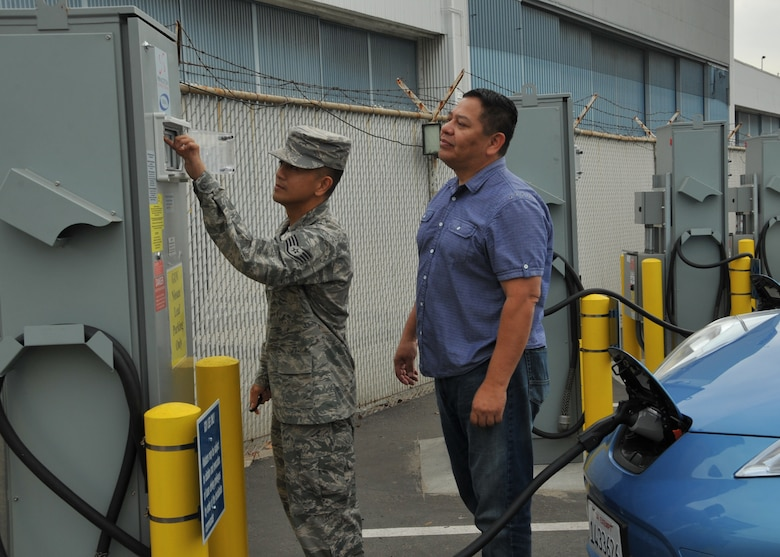 Staff Sgt Rey Sedantes (left), receives instruction on how to operate the Princeton bidirectional electric vehicle charging stations from vehicle operations contractor, Oscar Machado, right, during a training demo Oct. 31, 2014, in El Segundo, Calif. The charging stations will charge the electric vehicles directly from the local utility grid enabling Los Angeles Air Force Base personnel to utilize the electric vehicles as transportation within the base. When called-upon, and when connected to the electric vehicle, the bidirectional charging station will switch power flow directions in order to support vehicle-to-grid energy request by discharging the electric vehicle's onboard battery. Sedantes is with the 61st Civil Engineering and Logistics Squadron. (U.S. Air Force photo/Sarah Corrice)