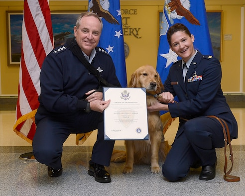 "Air Force Chief of Staff Gen. Mark A. Welsh III (left) promotes 2nd Lt. Goldie, a therapy dog from Walter Reed National Military Medical Center, to the rank of major, with Maj. Regina Owens, a psychiatric nurse, Nov. 12, 2014, in the Pentagon. The ceremony highlights one of the secretary of the Air Force priorities, ""Taking Care of People."" Goldie, along with a team of therapy dogs, provides comfort to the hospital's patients and family members.  (U.S. Air Force photo/Scott M. Ash)"