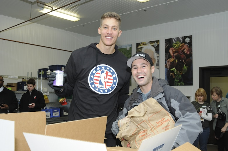 Tech. Sgt. Jacob Goodwin, a recruiter with Oregon National Guard Joint Force Headquarters who is stationed in Portland, pauses with Meyers Leonard, center for the Portland Trail Blazers, while packing food boxes to support the Oregon Food Bank. (U.S. Air National Guard photo by Capt. Angela Walz, 142nd Fighter Wing Public Affairs)