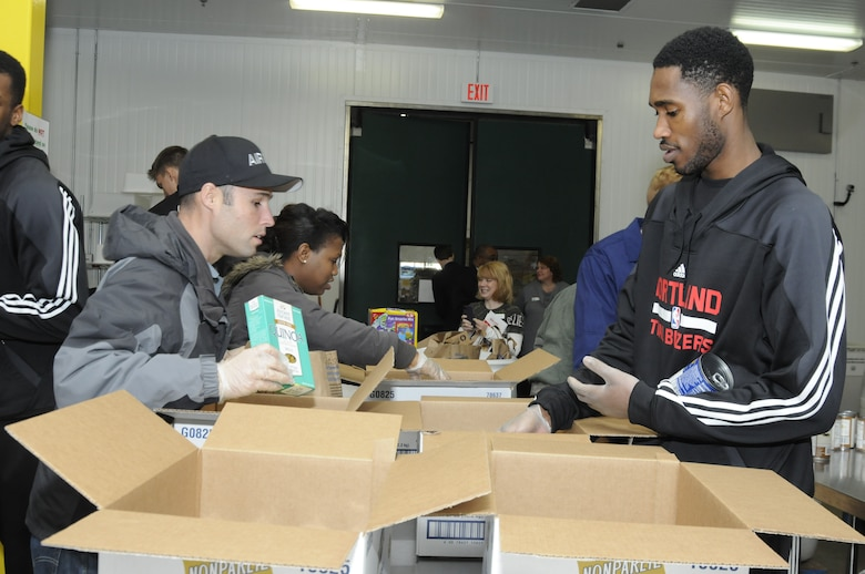 Tech. Sgt. Jacob Goodwin, a recruiter with Oregon National Guard Joint Force Headquarters who is stationed in Portland, works with Will Barton, a guard for the Portland Trail Blazers, as they pack food boxes to support the Oregon Food Bank. (U.S. Air National Guard photo by Capt. Angela Walz, 142nd Fighter Wing Public Affairs)