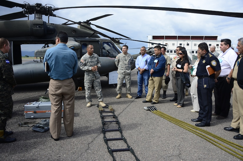 U.S. Army Sgt. Maynor Oliva, crew chief with the 1-228th Aviation Regiment, briefs Joint Task Force-Bravo's Honduran Leaders' Day guests on the capabilities of a UH-60L Black Hawk helicopter at Soto Cano Air Base, Honduras, Nov. 14, 2014.  Over 40 leaders from around the Republic of Honduras came to learn more about the mission and capabilities of JTF-Bravo and Soto Cano Air Base. (U.S. Air Force photo/Tech. Sgt. Heather Redman)