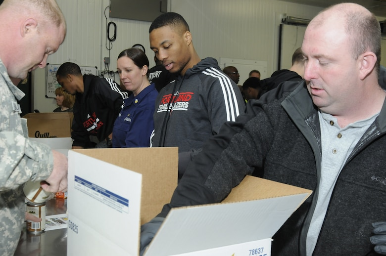 Tech. Sgt. Neil Bohne (right), 142nd Fighter Wing Aircrew Flight Equipment, talks with Damian Lillard, a guard for the Portland Trail Blazers, as they pack food boxes to support the Oregon Food Bank. (U.S. Air National Guard photo by Capt. Angela Walz, 142nd Fighter Wing Public Affairs)