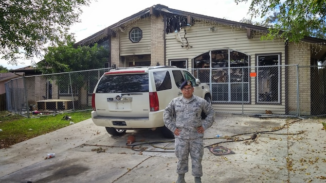 Senior Airman Christopher Taylor, 802nd Security Forces Squadron pass and processing, stands outside the remains of the burnt building in San Antonio. Taylor saved a disabled man from a fire, Nov. 3. The man was admitted to the San Antonio Military Medical Complex where he remains for treatment due to minor burns on the left side of his body and severe smoke inhalation. (U.S. Air Force photo by Senior Airman Lynsie Nichols/released).