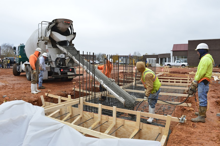 MCGHEE TYSON AIR NATIONAL GUARD BASE, Tenn. - Construction crewmen pour the concrete for the footings of the classroom and dormitory facility retaining wall here Nov. 13, 2014. Due to current weather conditions this concrete must set for at least a week before the crew can continue building the 17 foot tall wall. (U.S. Air National Guard photo by Master Sgt. Jerry D. Harlan/Released)