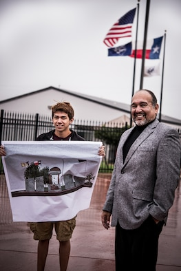 Julio Zamora, a senior at South San Antonio High School, and architect Jorge Flores stand near the site of where the War Heroes Memorial will be built. Zamora holds a transcribed illustration of his design, Nov. 6, 2014, which was created in a program used by professional architects to manipulate various architectural symbols. The memorial is meant to commemorate native San Antonio veterans, from across the military services, who have lost their lives serving their country. (U.S. Air Force photo illustration by 1st Lt. Jose R. Davis)