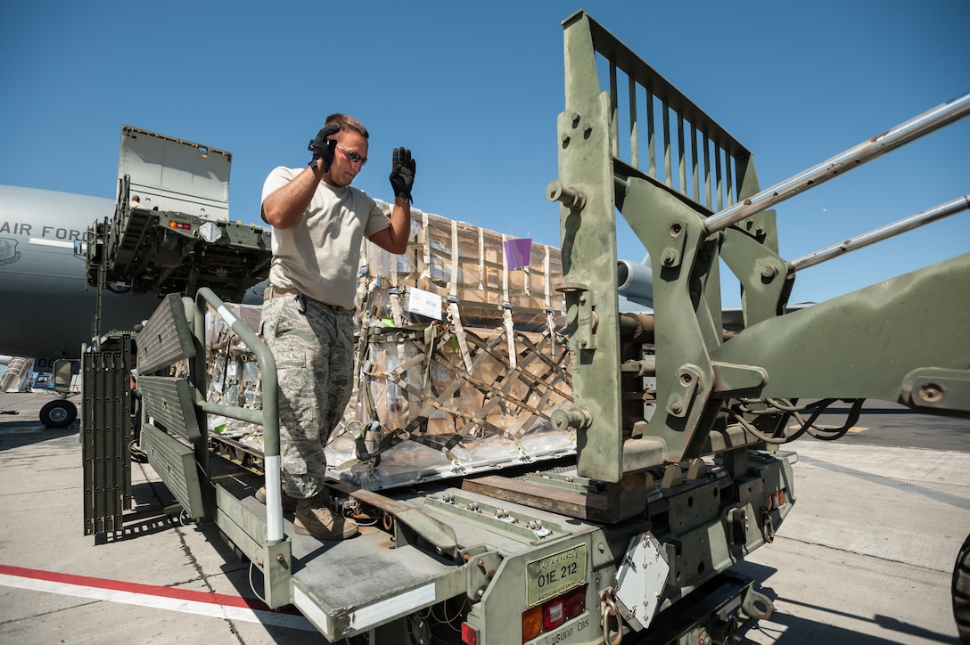 U.S. Air Force Tech. Sgt. Brian Leach, an aerial porter from the Kentucky Air National Guard's 123rd Contingency Response Group, directs the positioning of a forklift to offload pallets of humanitarian aid from a Halverson cargo-handling vehicle at Léopold Sédar Senghor International Airport in Dakar, Senegal, Nov. 12, 2014. The cargo will be staged in Senegal before being transloaded to U.S. Air Force C-130J aircraft for delivery into Monrovia, Liberia, in support of Operation United Assistance, the U.S. Agency for International Development-led, whole-of-government effort to contain the Ebola virus outbreak in West Africa. (U.S. Air National Guard photo by Maj. Dale Greer)
