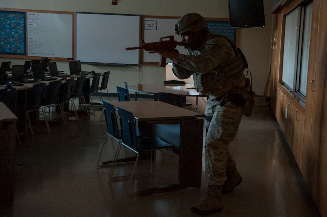 Staff Sgt. Carl Higgins, 51st Security Forces Squadron patrolman, clears a classroom for threats during an active shooter exercise at Osan Air Base, Republic of Korea, Nov. 13, 2014. All Osan Schools conducted a lockdown/shelter in place drills simultaneous to the active shooter exercise. (U.S. Air Force photo by Senior Airman Matthew Lancaster)
