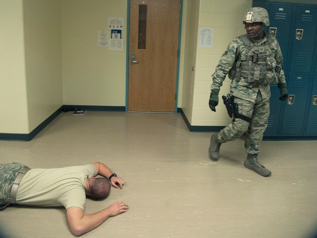Staff Sgt. Pierre Johnson, 51st Security Forces Squadron patrolman, checks the body of the shooter during an active shooter exercise at Osan Air Base, Republic of Korea, Nov. 13, 2014. Active shooter exercises are done to prepare responders for real-world scenario. (U.S. Air Force photo by Senior Airman Matthew Lancaster)