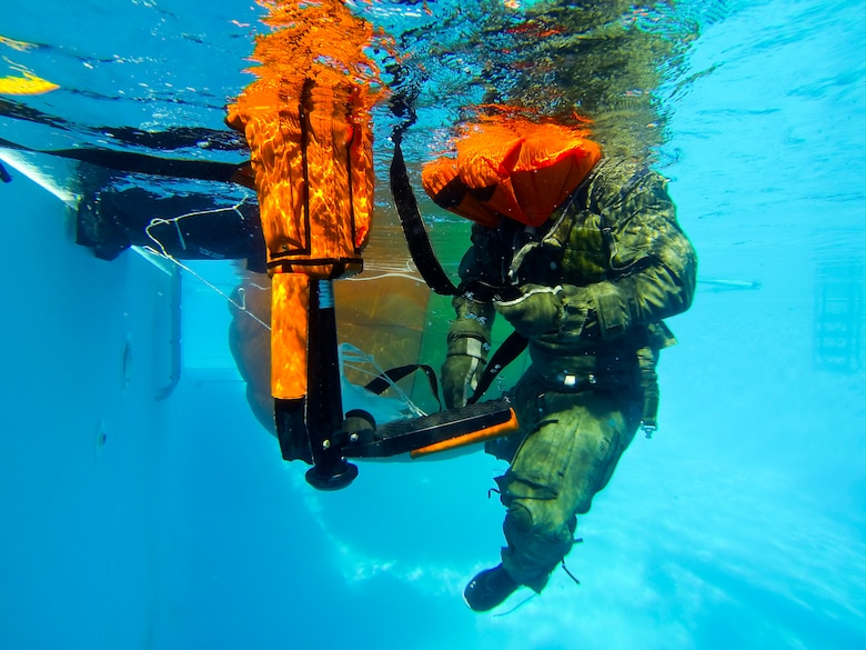Lt. Col. Ben Aronhime positions himself on a forest penetrator, a rescue device used in water rescues, during water survival class Oct. 31, 2014, on Eglin Air Force Base, Fla. Pilots attending F-35 Lightning II water survival training are placed in simulated scenarios to provide them with the knowledge they need if they were to eject over water. The 33rd Operations Support Squadron F-35 Lightning II flight equipment shop incorporated some training elements from previous water survival training programs and developed training tools and techniques to account for the new equipment unique to the F-35 program. Aronhime is a 56th Training Squadron pilot. (U.S. Air Force photo/Staff Sgt. Marleah Robertson)