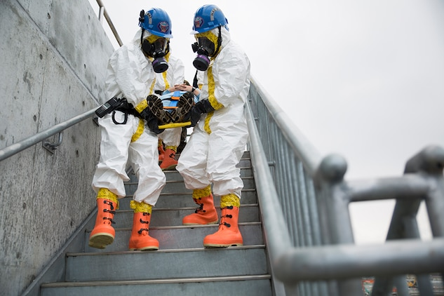Fire fighters with the Marine Corps Air Station Iwakuni Fire Station extract a victim from the fire training tower during Chemical Biological Radiological Nuclear and Hazardous Material Emergency Response Operations aboard MCAS Iwakuni, Japan, Nov. 8, 2014. This was the first time the MCAS Iwakuni Fire Station, Marine Aircraft Group 12 and the Japan Ground Self-Defense Force's 102nd Central Nuclear Biological Chemical Weapon Defense Unit collaborated to conduct this type of training.