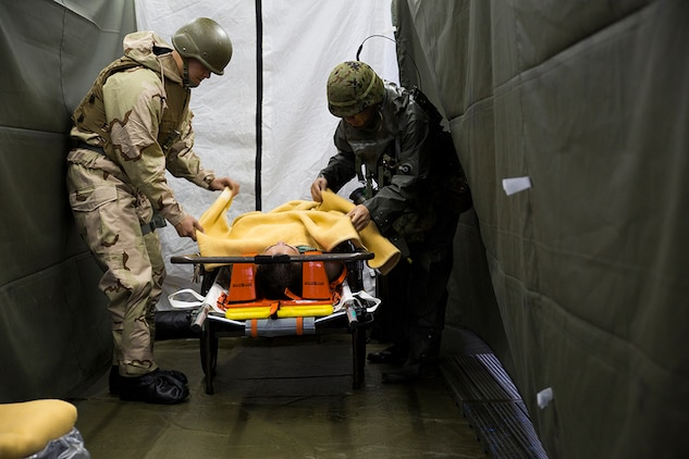 A Marine with Marine Aircraft Group 12 and a member of the Japan Ground Self-Defense Force's 102nd Central Nuclear Biological Chemical Weapon Defense Unit take care of a victim during Chemical Biological Radiological Nuclear and Hazardous Material Emergency Response Operations aboard MCAS Iwakuni, Japan, Nov. 8, 2014. This was the first time the MCAS Iwakuni Fire Station, Marine Aircraft Group 12 and the Japan Ground Self-Defense Force's 102nd Central Nuclear Biological Chemical Weapon Defense Unit collaborated to conduct this type of training.
