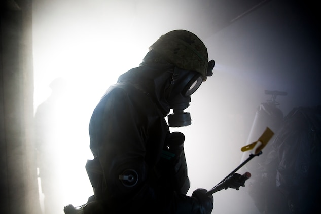 2nd Central Nuclear Biological Chemical Weapon Defense Unit makes his way through a smoke filled room inside the fire training tower aboard Marine Corps Air Station Iwakuni, Japan, Nov. 7, 2014. The 102nd Central NBC Weapon Defense Unit, Marine Aircraft Group 12, and the MCAS Iwakuni Fire Station collaborated to conduct interoperability training while executing Chemical Biological Radiological Nuclear and Hazardous Material Emergency Response Operations.