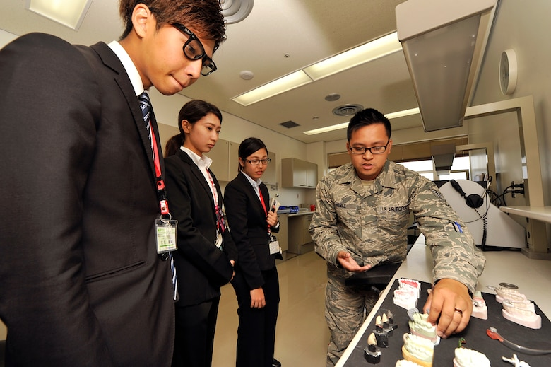 U.S. Air Force Staff Sgt. Jet Nesle, 18th Dental Squadron NCO in charge of radiology, shows teeth molds to students from the Nikkei College of Business in Okinawa City during a base facility tour on Kadena Air Base, Japan, Nov. 14, 2014. The program allows the U.S. military to support the local community by hosting a program for local students to help improve their English skills. (U.S. Air Force photo/Naoto Anazawa)