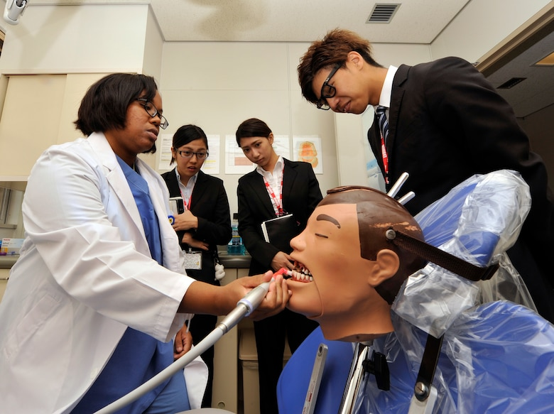 U.S. Air Force Staff Sgt. Consuelo Cabrera, 18th Dental Squadron preventive dentistry technician, demonstrates cleaning teeth on a mannequin for students from the Nikkei College of Business in Okinawa City during a base facility tour on Kadena Air Base, Japan, Nov. 14, 2014. The program supports the local community by hosting students to help improve their English skills. It also offers an opportunity for Air Force members to interact with the students and show what the Air Force does during facility tours. (U.S. Air Force photo/Naoto Anazawa)