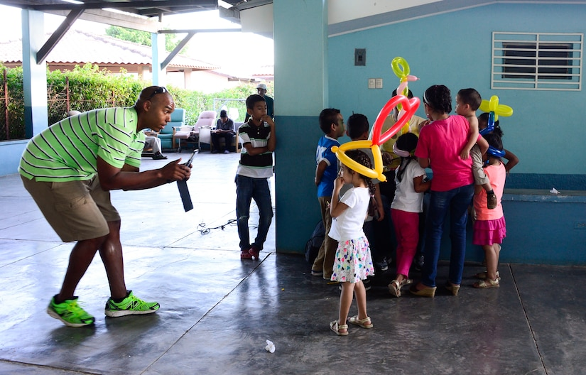 U.S. Army Maj. Darwin Maull, Joint Task Force-Bravo operations strategist, takes pictures of a young girl with a balloon hat during a visit to the Sisters of Charity Orphanage in Comayagua, Honduras, Nov. 16, 2014.  The Sisters of Charity Orphanage is one of seven different orphanages from around the Comayagua Valley that the U.S. military personnel assigned to JTF-Bravo have supported over the past 17 years. In addition to spending time with interacting with children, members have also collected and donated much-needed supplies and food, as well as helped in minor construction work on the buildings in which the children live. (U.S. Air Force photo/Tech. Sgt. Heather Redman)