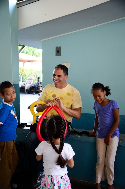 U.S. Air Force Master Sgt. Carlos Hampton, non-commissioned officer in charge of Air Traffic Control Training and Standardization for the 612th Air Base Squadron, makes balloon hats for children from the Sisters of Charity Orphanage in Comayagua, Honduras, Nov. 16, 2014.  The Sisters of Charity Orphanage is one of seven different orphanages from around the Comayagua Valley that the U.S. military personnel assigned to JTF-Bravo have supported over the past 17 years. In addition to spending time with interacting with children, members have also collected and donated much-needed supplies and food, as well as helped in minor construction work on the buildings in which the children live. (U.S. Air Force photo/Tech. Sgt. Heather Redman)