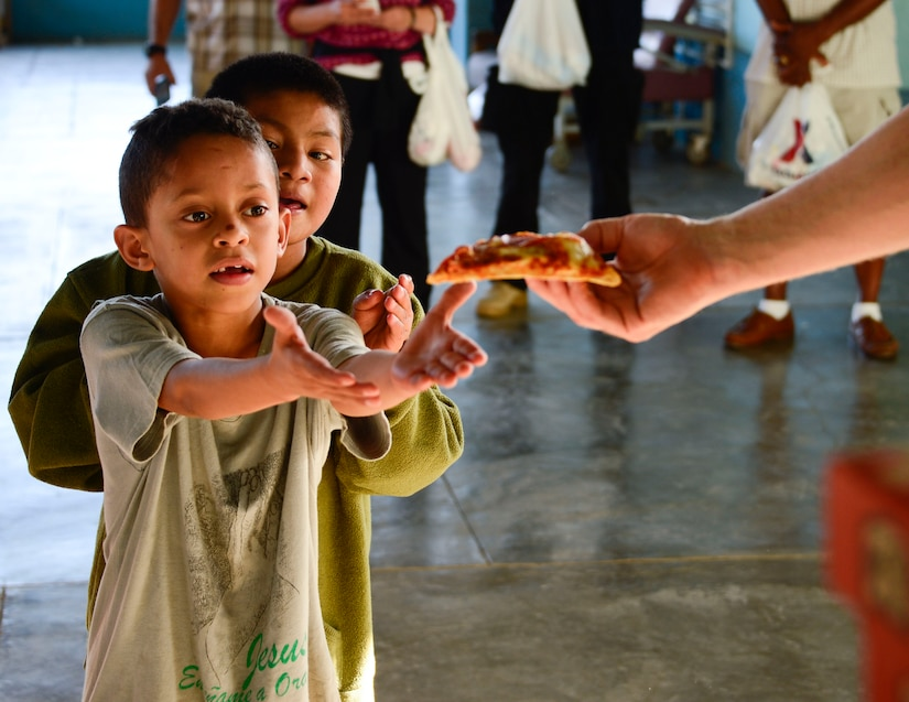 A young boy receives a slice of pizza from U.S. Air Force Capt. Samuel McClellan, Joint Task Force-Bravo command chaplain, during the Friendship Chapel's sponsored visit to the Sisters of Charity Orphanage in Comayagua, Honduras, Nov. 16, 2014.  The Sisters of Charity Orphanage is one of seven different orphanages from around the Comayagua Valley that the U.S. military personnel assigned to JTF-Bravo have supported over the past 17 years. In addition to spending time with interacting with children, members have also collected and donated much-needed supplies and food, as well as helped in minor construction work on the buildings in which the children live. (U.S. Air Force photo/Tech. Sgt. Heather Redman)