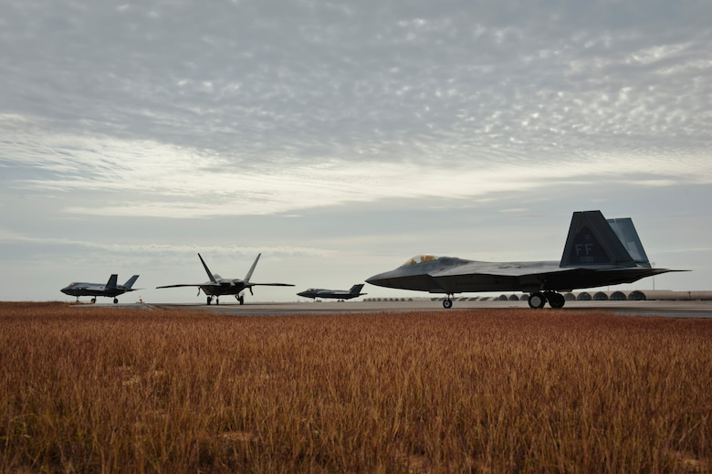 F-22 Raptors from the 94th Fighter Squadron, Joint Base Langley-Eustis, Virginia, and F-35A Lightning IIs from the 58th Fighter Squadron, Eglin Air Force Base, Florida, perform final preflight checks before taking off for an integration training mission on Eglin Training Range, Florida, Nov. 6, 2014. The F-35s and F-22s flew offensive counter air, defensive counter air and interdiction missions, maximizing effects by employing fifth-generation capabilities together. (U.S. Air Force photo/Staff Sgt. Marleah Robertson)
