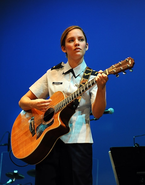 U.S. Air Force 2nd Lt. Carly Costello, 55th Wing Public Affairs Officer, plays guitar with the U.S. Air Force's Heartland of America Band at Blair High School on Nov. 8, 2014.  The Salute to Veterans concert Series was a five-day venture with thousands of attendees.  (U.S. Air Force photo by Josh Plueger/Released)