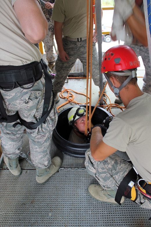 Staff Sgt. Nate Grys is lowered into a large pipe during a confined space exercise conducted by the firefighters of the 179th Airlift Wing, Ohio Air National Guard, during a training deployment to the Alpena Combat Readiness Training Center, Mich., Aug. 20, 2014. The firefighters spent a week at Alpena, training on live-fire exercises involving a simulated structure fire and aircraft fire, and on various rescue scenarios. (U.S. Air National Guard photo by Tech. Sgt. Dan Heaton)