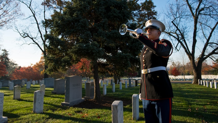Sgt. Jason Pena, a bugler with The United States Marine Corps Drum and Bugle Corps, plays taps after a wreath was placed at the grave site of Gen. Thomas Holcomb, the 17th commandant of the Marine Corps, in Arlington National Cemetery, Arlington, Va., Nov. 10, 2014. Holcomb served as the commandant of the Marine Corps from 1936 to 1943. (U.S. Marine Corps photo by Sgt. Melissa Karnath/Released)