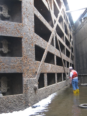 Robert Burstynowicz, a district structural engineer, inspects one of two miter gate leaves at the upstream end of the 84 ft x 600 ft chamber.