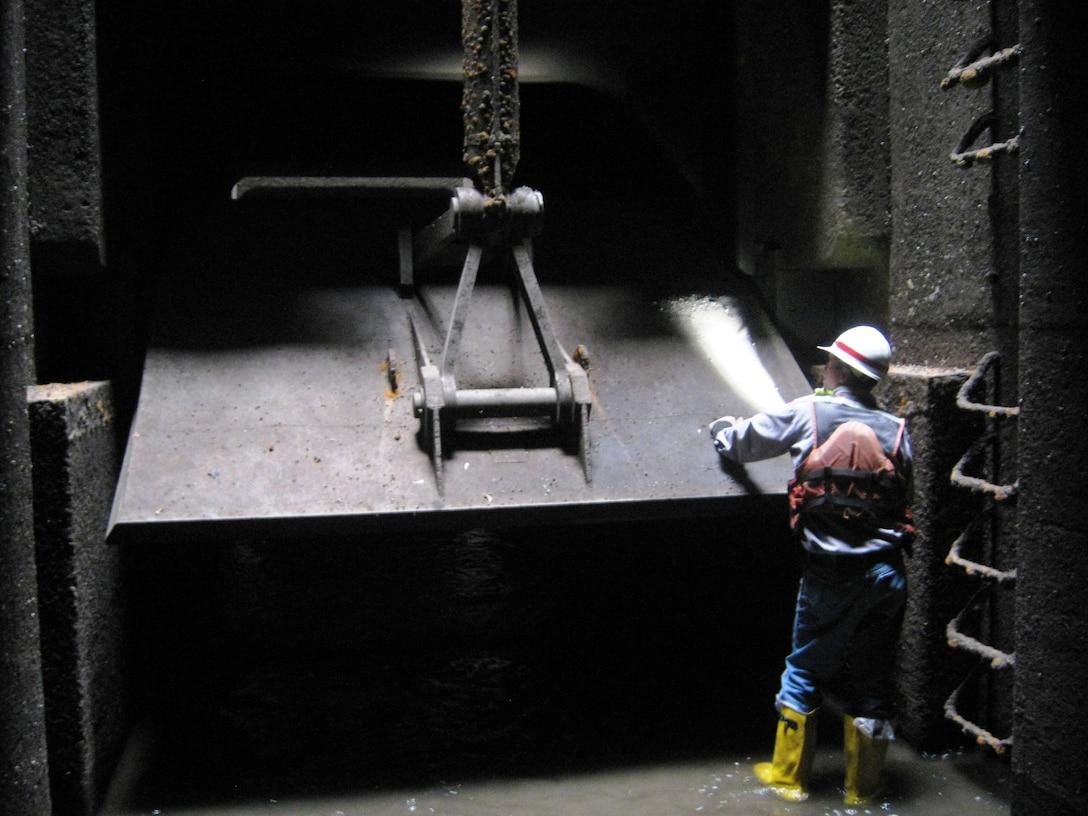 Bob Szemanski, a district maintenance mechanical supervisor, examines a valve inside the dewatered land wall culvert.