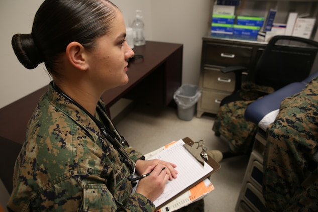 Petty Officer 3rd Class Heather Holcomb, corpsman, Task Force Aid Station, Ground Combat Element Integrated Task Force, records a patient report at the task force aid station, Nov. 6, 2014. From October 2014 to July 2015, the Ground Combat Element Integrated Task Force will conduct individual and collective skills training in designated combat arms occupational specialties in order to facilitate the standards based assessment of the physical performance of Marines in a simulated operating environment performing specific ground combat arms tasks. (U.S. Marine Corps photo by Cpl. Paul S. Martinez/Released)