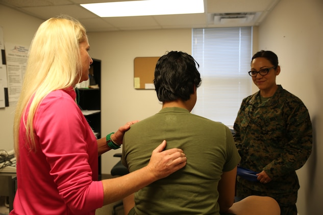 Corrine Ruttiger, left, athletic trainer, Ground Combat Element Integrated Task Force, and Petty Officer 2nd Class Beatriz Byer, right, corpsman, Task Force Aid Station, GCEITF, evaluate a patient at the athletic trainer's office, Nov. 6, 2014. From October 2014 to July 2015, the Ground Combat Element Integrated Task Force will conduct individual and collective skills training in designated combat arms occupational specialties in order to facilitate the standards based assessment of the physical performance of Marines in a simulated operating environment performing specific ground combat arms tasks. (U.S. Marine Corps photo by Cpl. Paul S. Martinez/Released)