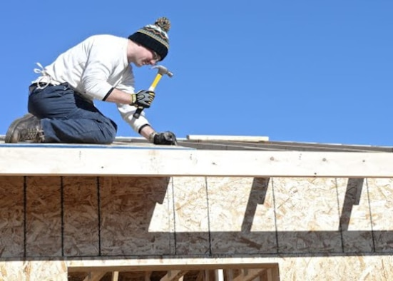 Senior Airman Travis Bellefeuille, 28th Operations Support Squadron targeteer, builds a roof during a Habitat for Humanity project in Summerset, S.D., Nov. 8, 2014. Bellefeuille and several other Ellsworth Airmen dedicated their time constructing a roof for a house that will be provided to a Habitat family in need. Habitat Black Hills Area volunteers have helped house over 300 people in the local area. (U.S. Air Force photo by Senior Airman Anania Tekurio/Released)