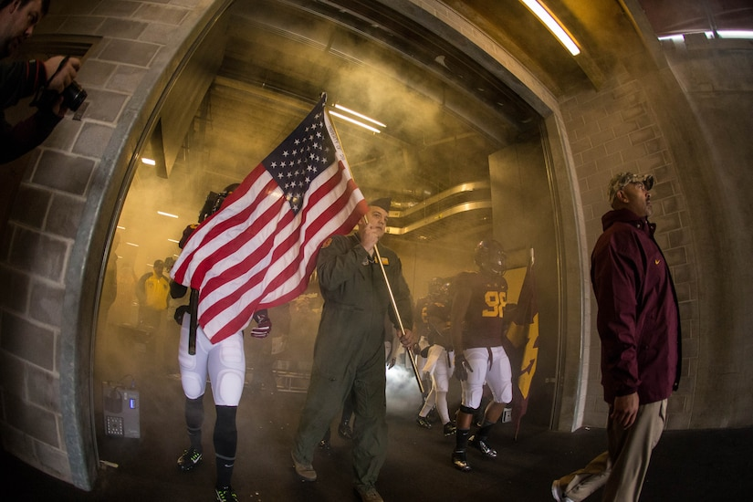 Technical Sergeant Ryan Radunzel, 16th Airlift Squadron loadmaster, prepares to run onto the field with the University of Minnesota football team Nov. 8, 2014, at TCF Bank Stadium, Minneapolis, Mn. Radunzel was selected by the university to carry the United States flag in honor of Veterans Day. The Gophers took on the University of Iowa Hawkeyes and defeated them 51-14. (University of Minnesota photo / Brace Hemmelgarn)
