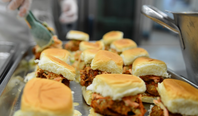 "Buffalo chicken sliders are arranged by a 52nd Force Support Squadron Airman during the ""Messlords"" luncheon at the Mosel Dining Facility on Spangdahlem Air Base, Germany, Nov. 15, 2014. Other items served during the luncheon included burger sliders, fish tacos and an assortment of salsas. (U.S. Air Force photo by Airman 1st Class Luke Kitterman/Released)"