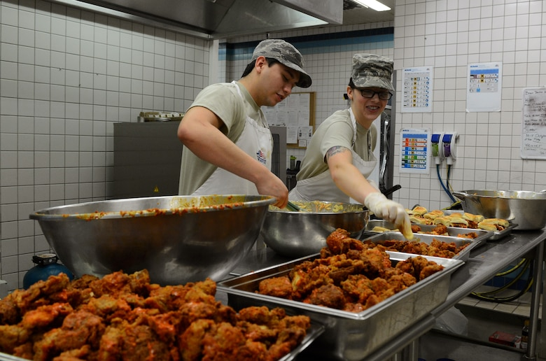 "Airmen from the 52nd Force Support Squadron prepare buffalo chicken sliders during the ""Messlords"" luncheon at the Mosel Dining Facility at Spangdahlem Air Base, Germany, Nov. 15, 2014. The Airmen worked with ""Messlords"" John Conley, owner and chef at Salsa Brava Mexican Grill in Flagstaff, Ariz., and Sarah Simington, owner and chef at Blue Moon Café in Baltimore. (U.S. Air Force photo by Airman 1st Class Luke Kitterman/Released)"
