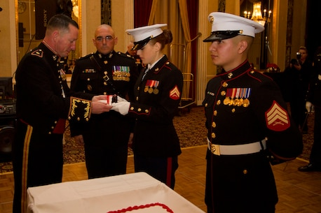 Maj. Charles D. Godwin, Commanding Officer of Recruiting Station Milwaukee, presents the birthday cake to the youngest Marine, Cpl. Victoria McKenzie, during RS Milwaukee's Birthday Ball ceremony Nov. 15, 2014.  The birthday cake is passed from the oldest to the youngest Marine present, symbolizing the passing of history and traditions to the next generation.  Cpl. McKenzie is the Operations Clerk for RS Milwaukee.