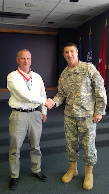 The Tulsa District Commander, Col. Richard A. Pratt, shakes hands with Wade Anderson, director of the Southwestern Division Dam Safety Production center, after presenting him with a bronze de Fleury medal.