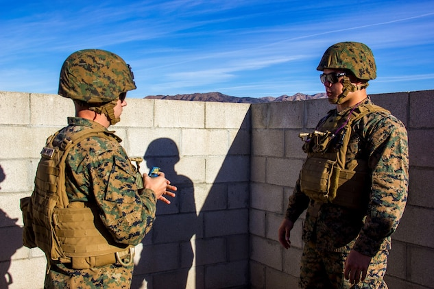 Corporal Ronald Peebles, right, a motor transport operator with Headquarters Battery, 5th Battalion, 11th Marine Regiment, instructs another Marine on proper grenade throwing techniques during a hand grenade training exercise aboard Marine Corps Base Camp Pendleton, Calif., Nov. 18, 2014. The event served as a way for 5/11 Marines to refresh their basic fighting skills and to maintain their combat mindsets.