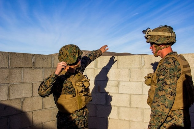 Corporal Ronald Peebles, left, a motor transport operator with Headquarters Battery, 5th Battalion, 11th Marine Regiment, from Waikiki, Hawaii, prepares to throw an M-69 practice grenade during a hand grenade training exercise aboard Marine Corps Base Camp Pendleton, Calif., Nov. 18, 2014. The event helped Marines of 5/11 refresh their basic combat skills and maintain their combat mindsets.