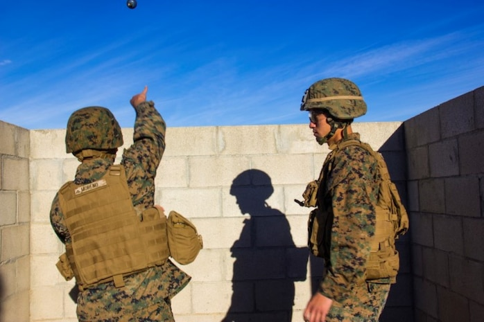 Lance Cpl. George Moreno, left, an electro-optical ordnance repairman with Headquarters Battery, 5th Battalion, 11th Marine Regiment, from San Antonio, throws an M-69 practice grenade during a hand grenade training exercise aboard Marine Corps Base Camp Pendleton, Calif., Nov. 18, 2014. The event helped Marines of 5/11 refresh their basic combat skills and maintain their combat mindsets.
