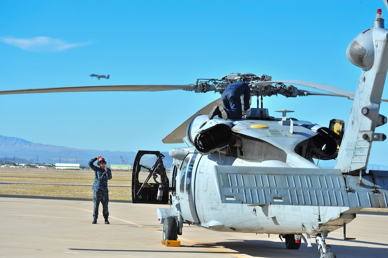Sailors detached from Helicopter Sea Combat Squadron 4,Naval Air Station North Island, San Diego, Calif., perform preflight checks on a Navy MH-60S Knighthawk as an A-10C Thunderbolt II flies in the background at Davis-Monthan Air Force Base, Ariz., Nov. 13, 2014.  HSC-4 conducted joint training with D-M A-10C Thunderbolt II squadrons and Combat Search and Rescue units to strengthen operations between the services.  (U.S. Air Force Photo by Airman 1st Class Chris Massey/Released)