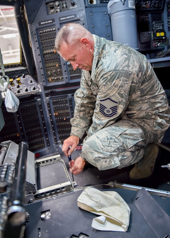 Master Sgt. Ed Shaffer, an aircraft maintenance craftsman with the 910th Maintenance Squadron, loosens an armor plating fastener in the flight deck of a C130 Hercules aircraft here, Nov. 6, 2014. Youngstown is the second base to receive a test version of the new system, designed for easier and more secure installation and better protection for aircrew members. (U.S. Air Force photo/Eric M. White)