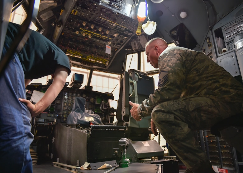 Master Sgt. Ed Shaffer, an aircraft maintenance craftsman with the 910th Aircraft Maintenance Squadron, examines a new armor plating system with a contractor in the flight deck of a C-130 Hercules aircraft here, Nov. 6, 2014. Youngstown is the second base to receive a test version of the new system, designed for easier and more secure installation and better protection for aircrew members. (U.S. Air Force photo/Eric M. White)