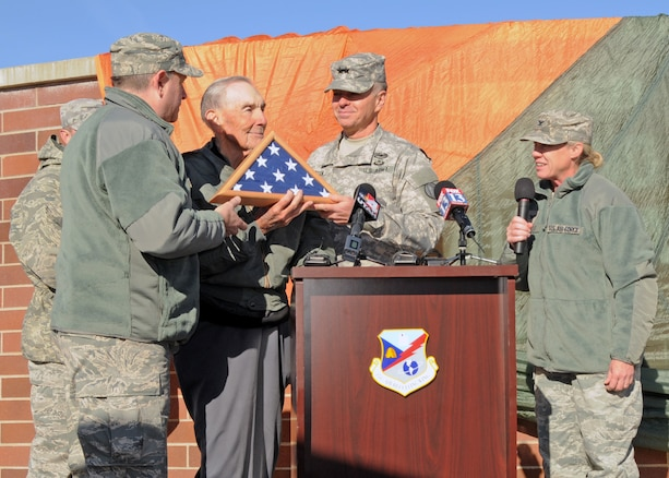 Maj. Gen. Jefferson Burton, Adjutant General of the Utah National Guard, presents a flag to retired Air Force Brig. Gen. Roland R. Wright during a ceremony to rename the Utah Air National Guard Base in his honor held in Salt Lake City, Utah on Nov. 18, 2014. The flag was flown over the Roland R. Wright Air National Guard base, as well as on a KC-135 Stratotanker mission. Wright, a combat pilot with a distinguished military career spanning more than three decades, served as Utah's first Chief of Staff for Air. (Air National Guard photo by Staff Sgt. Annie Edwards/RELEASED)